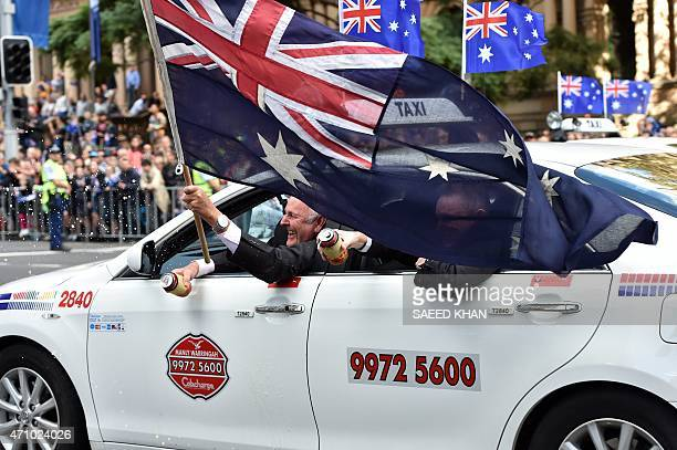 Veterans wave a national flag from a taxi during the the Anzac Day parade along George Street in Sydney on April 25 2015 Record numbers of...