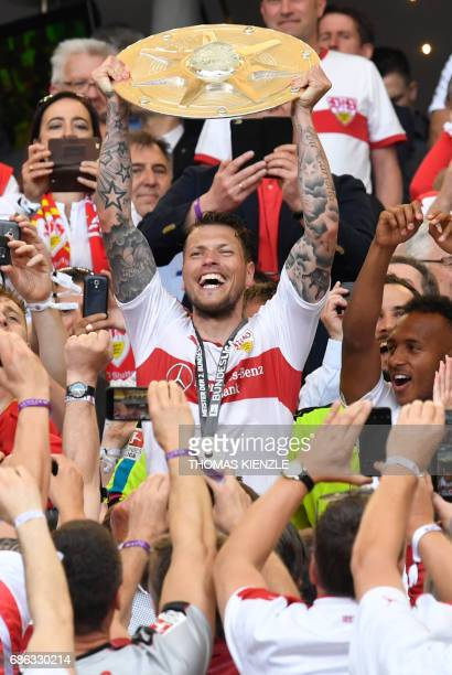 VfB Stuttgart's forward Daniel Ginczek holds up the trophy for the championship title after the German second division Bundesliga football match VfB...