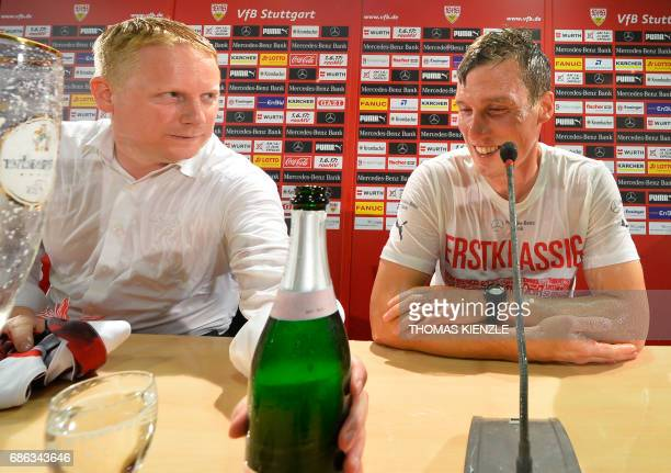 VfB Stuttgart's head coach Hannes Wolf and director sports Jan Schindelmeiser sit on the podium after their players showered them with beer during...