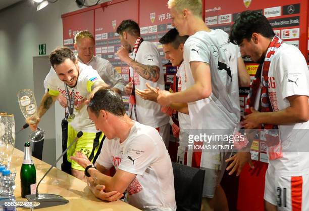 VfB Stuttgart's head coach Hannes Wolf sits on the podium after his players showered him with beer during the press conference after the German...