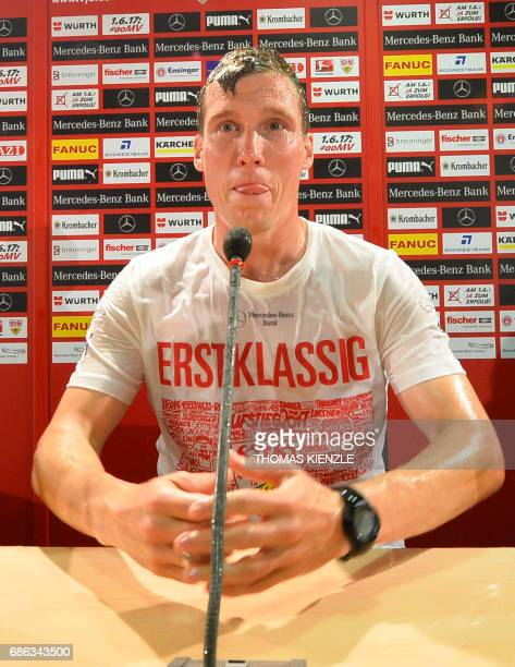 VfB Stuttgart's head coach Hannes Wolf sits on the podium after his players showered him with beer and champagne during the press conference after...
