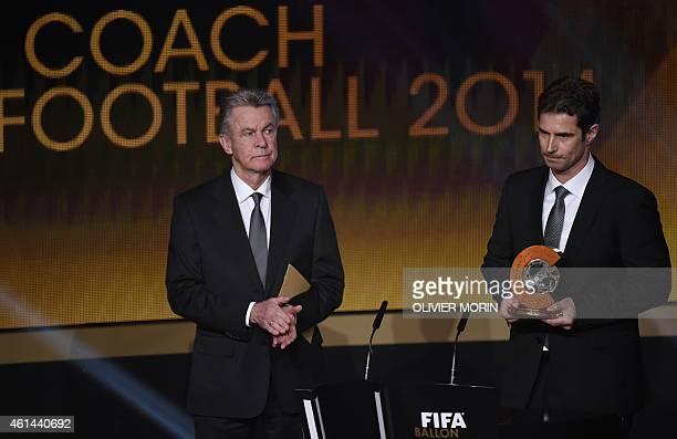 VfL Wolfsburg's German coach Ralf Kellermann stands on stage after receiving from Switzerland's German coach Ottmar Hitzfeld the 2014 FIFA World...