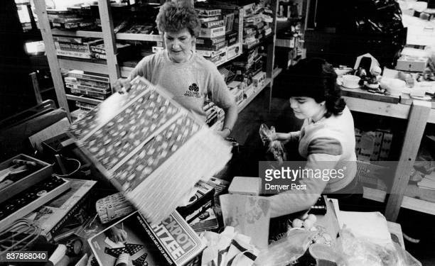 Vi Kules and Milena Zunga work at sorting the thousands of old games that will distributed by the Jeffco Action Center as part of a Santa's shop Some...