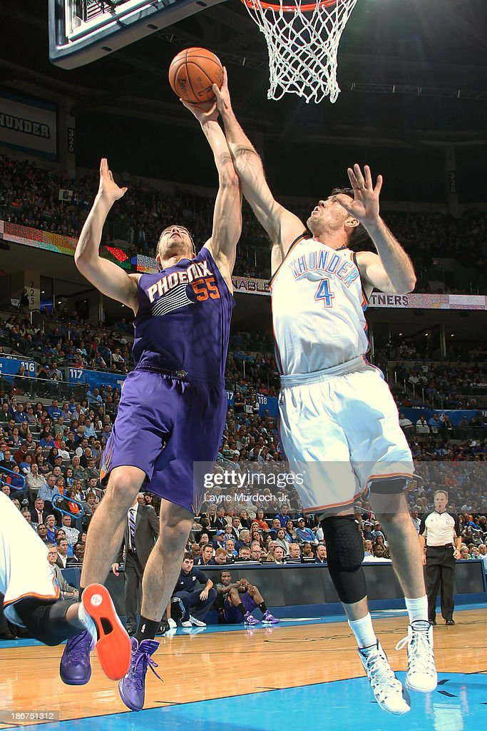 Viacheslav Kravtsov of the Phoenix Suns goes up for a rebound against Nick Collison of the Oklahoma City Thunder on November 03 2013 at the...
