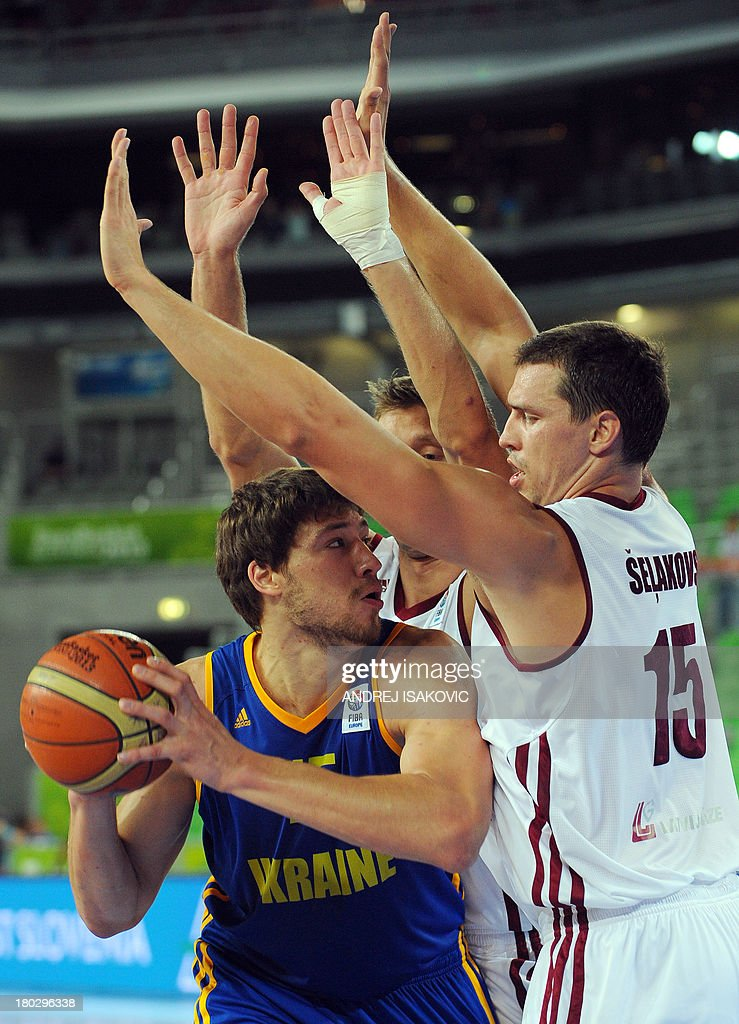 Viacheslav Kravtsov of Ukraine (L) vies with Andrejs Selakovs (R) and Kaspars Berzins of Latvia during the FIBA EuroBasket second round Group E basketball championship qualification match between Latvia and Ukraine, in Ljubljana, Slovenia, on September 11, 2013.