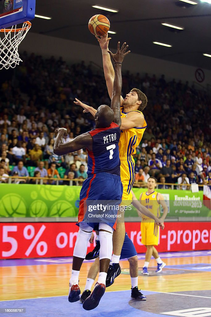 Viacheslav Kravtsov of Ukriane shoots over Johan Petro of France during the FIBA European Championships 2013 first round group A match between...