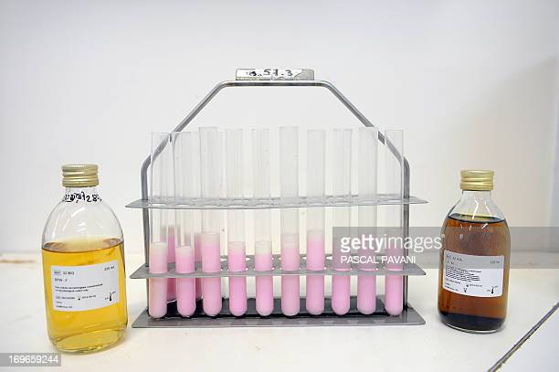 Vials of raw sheep's milk are pictured on May 29 2013 in SaintAffrique southern France with bottles of substances used to check the milk for strains...