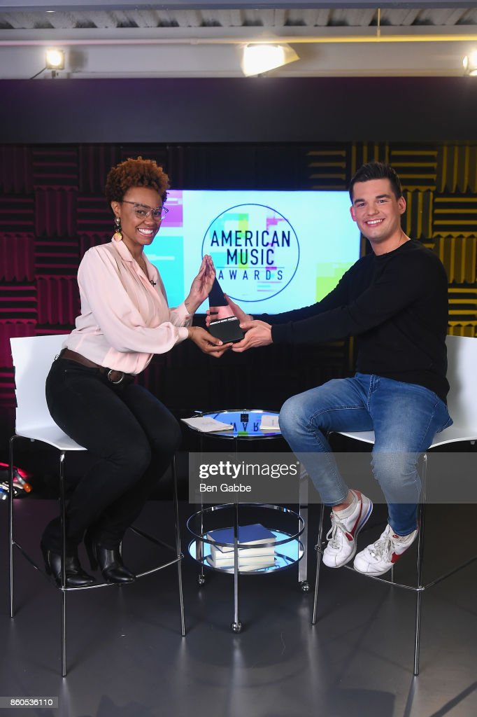 Vibe Editor and Billboard News Correspondent Shenequa Golding (L) and Billboard News Host Kevan Kenney pose with the American Music Awards trophy during the 2017 American Music Awards nominations announcement at Billboard on October 12, 2017 in New York City.