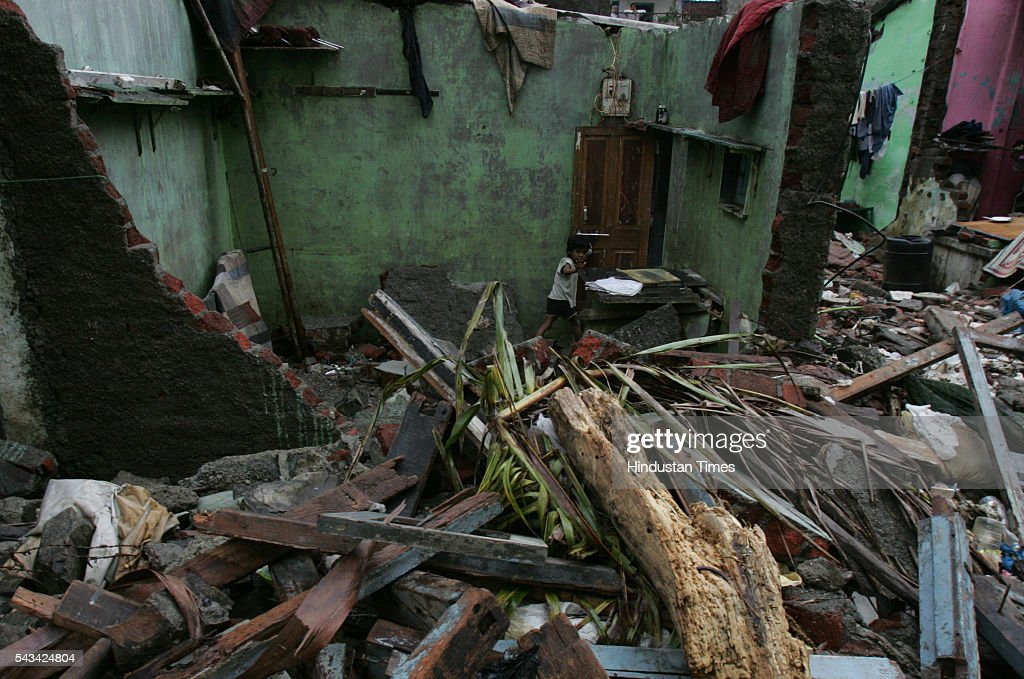 Vibha walks along the rubble caused by a wall collapse that eventually led to the flooding of the Indian Airlines colony at Kalina on August 2, 2005 in Mumbai, India.