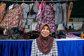 Viboonsri Wongsangiym poses with her clothing for sale at a local market Wiboonsri and her husband Bang Aree have made a living by producing Muslim...