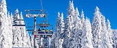 Vibrant active people winter image with skiers sitting on the ski lift, ski slope among white snow pine trees, blue sky