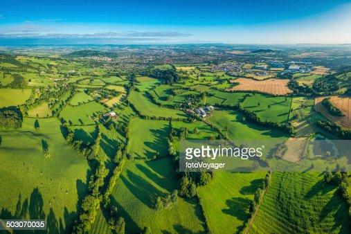 Vibrant green fields lush pasture farmland around town aerial photo