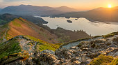 Sun rising above horizon at Derwentwater illuminating the landscape with vibrant Spring light.