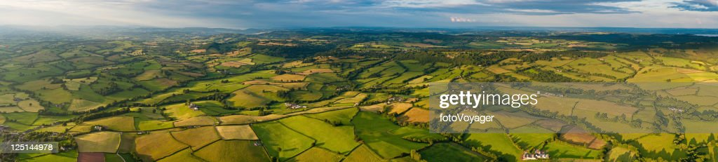 Vibrant patchwork landscape aerial panorama green fields farms country villages : Stock Photo