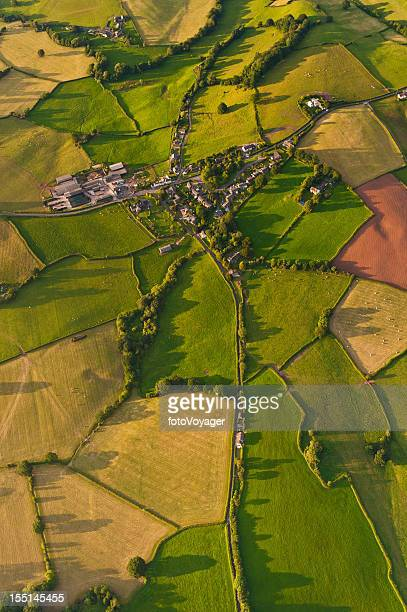 Vibrant patchwork landscape village summer fields