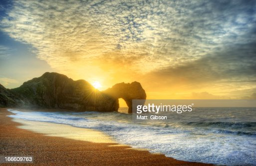 Vibrant sunrise over ocean with rock stack in foreground : Stock Photo