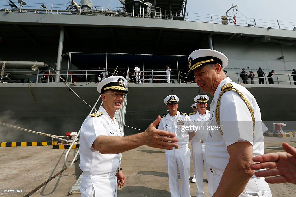 Vice Admiral Joseph P. Aucoin, Commander of the US Seventh Fleet (L) is greeted as he disembarks from the USS Blue Ridge in Shanghai on May 6, 2016. China will take part in a regular US-led naval exercise starting next month, Aucoin said on May 6, despite tensions over Beijing's territorial claims in the South China Sea. The visit of the USS Blue Ridge in the commercial hub of Shanghai comes just days after China denied a port call for a US aircraft carrier in its special administrative region of Hong Kong. / AFP / STR / China OUT