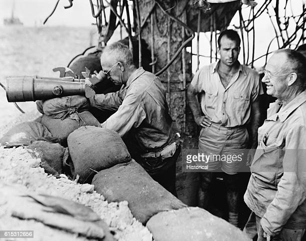 Vice Admiral Richmond Turner peers through captured Japanese field glasses at Tinian Island from Saipan two and onehalf miles away Lt General Holland...
