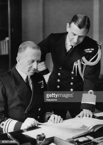 Vice Admiral Sir George Hamilton D'Oyly Lyon the new CommanderinChief of the Nore at his desk at Chatham England with his secretary Paymaster Captain...