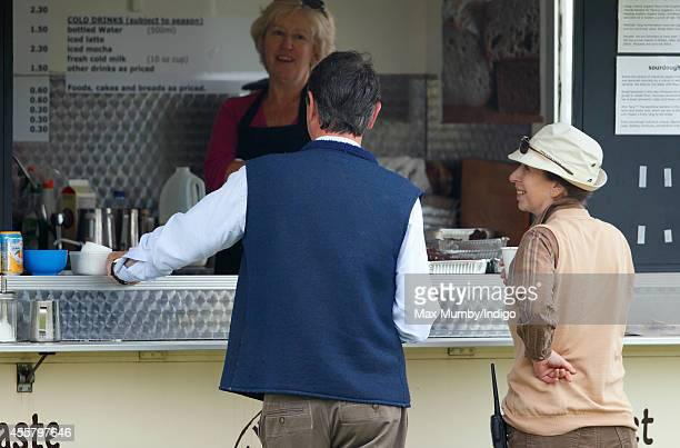 Vice Admiral Sir Tim Laurence and Princess Anne Princess Royal queue at a coffee stand as they attend the Whatley Manor International Horse Trials at...