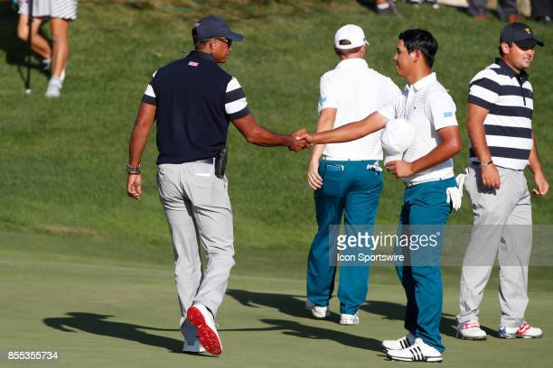 USA vice captain Tiger Woods shakes hands with International golfer Si Wook Kim on the 14th hole during the first round of the Presidents Cup on...