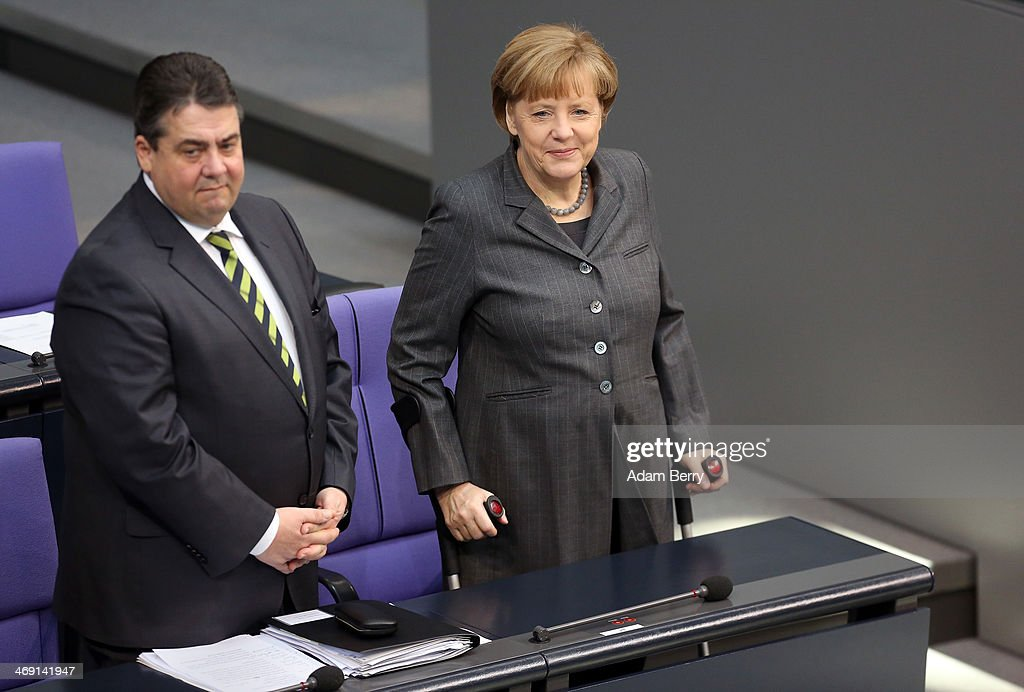 Vice Chancellor and Economy and Energy Minister <a gi-track='captionPersonalityLinkClicked' href=/galleries/search?phrase=Sigmar+Gabriel&family=editorial&specificpeople=543927 ng-click='$event.stopPropagation()'>Sigmar Gabriel</a> (SPD) (L) and German Chancellor <a gi-track='captionPersonalityLinkClicked' href=/galleries/search?phrase=Angela+Merkel&family=editorial&specificpeople=202161 ng-click='$event.stopPropagation()'>Angela Merkel</a> arrive for a meeting of the Bundestag, or German federal Parliament, on February 13, 2014 in Berlin, Germany. In a government policy statement, or Regierungserklaerung, Gabriel said he wants to see more financial strengthening of German cities and local communities, as well as an 8.50 EUR an hour minimum wage, a proposal met with opposition by Sahra Wagenknecht of the Left party (Die Linken), who insisted that 10 EUR an hour is a fairer salary.