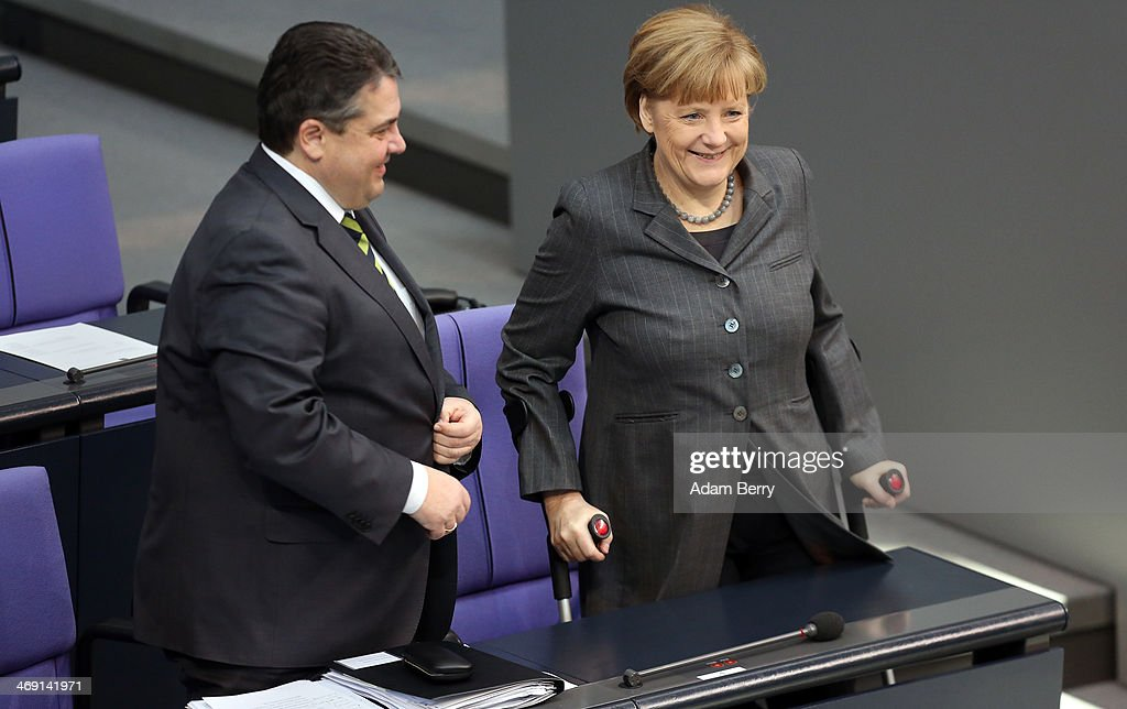 Vice Chancellor and Economy and Energy Minister Sigmar Gabriel (SPD) (L) and German Chancellor Angela Merkel arrive for a meeting of the Bundestag, or German federal Parliament, on February 13, 2014 in Berlin, Germany. In a government policy statement, or Regierungserklaerung, Gabriel said he wants to see more financial strengthening of German cities and local communities, as well as an 8.50 EUR an hour minimum wage, a proposal met with opposition by Sahra Wagenknecht of the Left party (Die Linken), who insisted that 10 EUR an hour is a fairer salary.