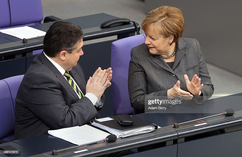 Vice Chancellor and Economy and Energy Minister <a gi-track='captionPersonalityLinkClicked' href=/galleries/search?phrase=Sigmar+Gabriel&family=editorial&specificpeople=543927 ng-click='$event.stopPropagation()'>Sigmar Gabriel</a> (SPD) (L) and German Chancellor <a gi-track='captionPersonalityLinkClicked' href=/galleries/search?phrase=Angela+Merkel&family=editorial&specificpeople=202161 ng-click='$event.stopPropagation()'>Angela Merkel</a> applaud during a meeting of the Bundestag, or German federal Parliament, on February 13, 2014 in Berlin, Germany. In a government policy statement, or Regierungserklaerung, Gabriel said he wants to see more financial strengthening of German cities and local communities, as well as an 8.50 EUR an hour minimum wage, a proposal met with opposition by Sahra Wagenknecht of the Left party (Die Linken), who insisted that 10 EUR an hour is a fairer salary.