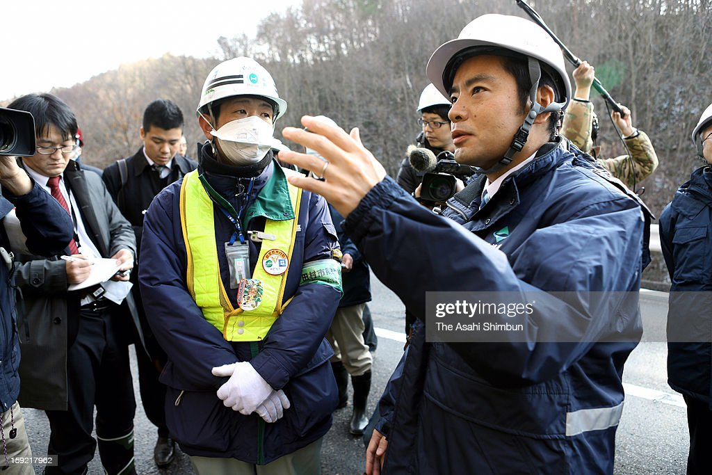 Vice Environment Minister Shinji Inoue (R) inspects a radioactive decontamination work on January 9, 2013 in Tamura, Fukushima, Japan. Environment Ministry Fukushima Office for Environmental Restoration confirmed at least two crooked cleanups, the workers had dumped tainted vegitation and water into the river, an explanatory meeting on January 10 for the government's plan on interim storage facility construction in Naraha town was cancelled as residents' angry backlash on the crooked cleanup.