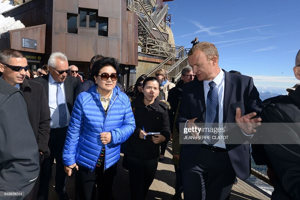 Vice Premier of China, Liu Yandong (L) listens to Mathieu Dechavanne (R), Director of 'La Compagnie du Mont-Blanc' which runs the ski resorts and tourist sites of the Chamonix-Mont Blanc valley, during Liu Yandong's visit on June 29, 2016 at the top of the Aiguille du Midi mountain above Chamonix, French Alps. / AFP / JEAN