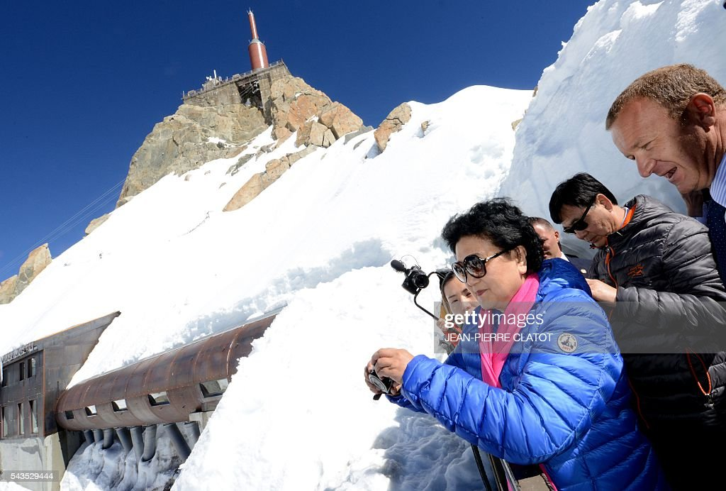 Vice Premier of China, Liu Yandong (C) listens to Mathieu Dechavanne (R), Director of 'La Compagnie du Mont-Blanc' which runs the ski resorts and tourist sites of the Chamonix-Mont Blanc valley, during Liu Yandong's visit on June 29, 2016 at the top of the Aiguille du Midi mountain above Chamonix, French Alps. / AFP / JEAN