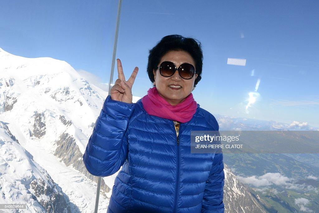 Vice Premier of China, Liu Yandong poses into the 'Step into the void' (Le Pas dans le Vide), a glass room attraction run by the Compagnie du Mont-Blanc, which operates the ski resorts and tourist sites of the Chamonix-Mont Blanc valley, during Liu Yandong's visit on June 29, 2016 at the top of the Aiguille du Midi mountain above Chamonix, French Alps. The 'Step into the Void' is a glass room with a glass floor, situated off the uppermost terrace of the Aiguille du Midi at an altitude of 3842 metres. It claims to be 'the highest attraction in Europe'. / AFP / JEAN