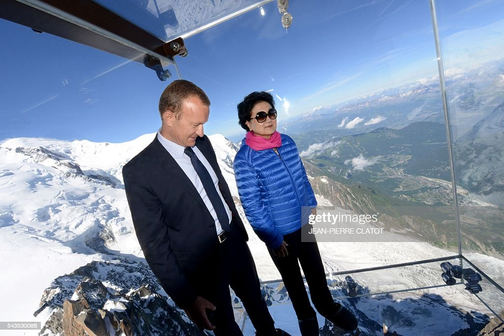 Vice Premier of China, Liu Yandong (R) poses with Mathieu Dechavanne, Director of 'La Compagnie du Mont-Blanc' which runs the ski resorts and tourist sites of the Chamonix-Mont Blanc valley, into the 'Step into the void' (Le Pas dans le Vide), a glass room attraction run by the Compagnie du Mont-Blanc, during Liu Yandong's visit on June 29, 2016 at the top of the Aiguille du Midi mountain above Chamonix, French Alps. The 'Step into the Void' is a glass room with a glass floor, situated off the uppermost terrace of the Aiguille du Midi at an altitude of 3,842 metres. It claims to be 'the highest attraction in Europe'. / AFP / JEAN