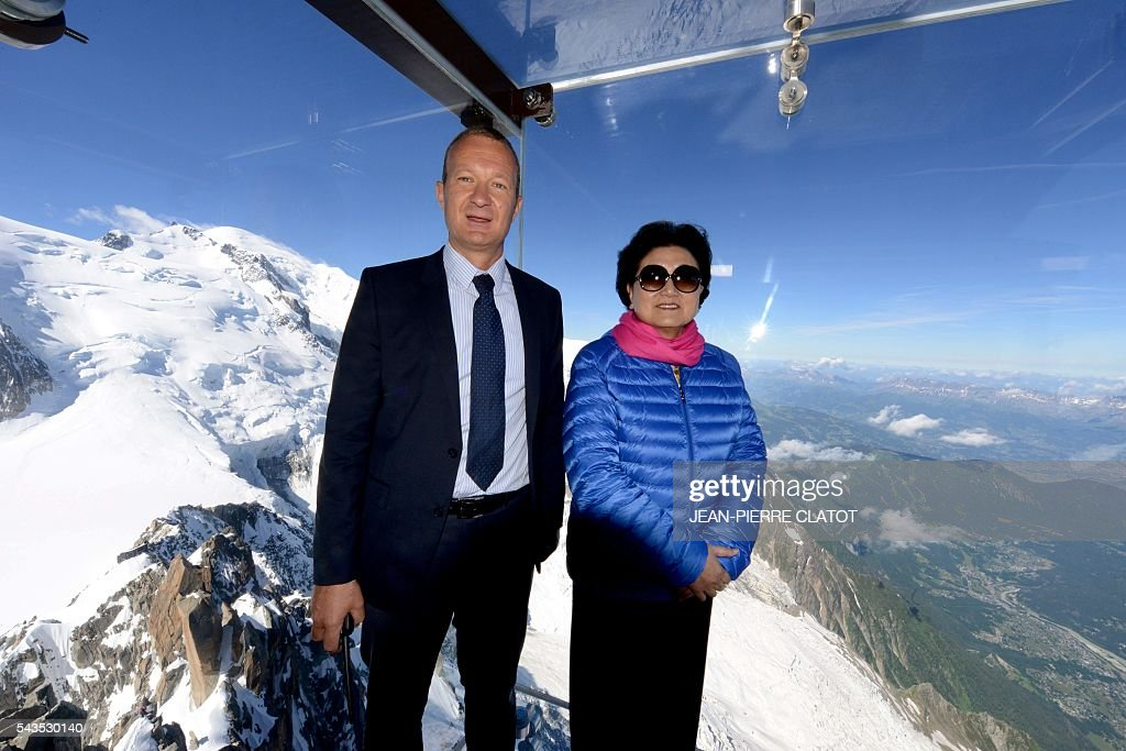 Vice Premier of China, Liu Yandong (R) poses with Mathieu Dechavanne, Director of 'La Compagnie du Mont-Blanc' which runs the ski resorts and tourist sites of the Chamonix-Mont Blanc valley, into the 'Step into the void' (Le Pas dans le Vide), a glass room attraction run by the Compagnie du Mont-Blanc, during Liu Yandong's visit on June 29, 2016 at the top of the Aiguille du Midi mountain above Chamonix, French Alps. The 'Step into the Void' is a glass room with a glass floor, situated off the uppermost terrace of the Aiguille du Midi at an altitude of 3842 metres. It claims to be 'the highest attraction in Europe'. / AFP / JEAN