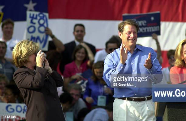 Vice President Al Gore smiles and claps his hands as his wife Tipper takes a photograph of him during a presidential rally August 14 2000 in downtown...