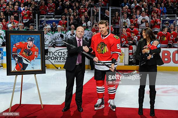 Vice president and general manager of the Chicago Blackhawks Stan Bowman presents Brad Richards with the 1000th career game hockey stick while...