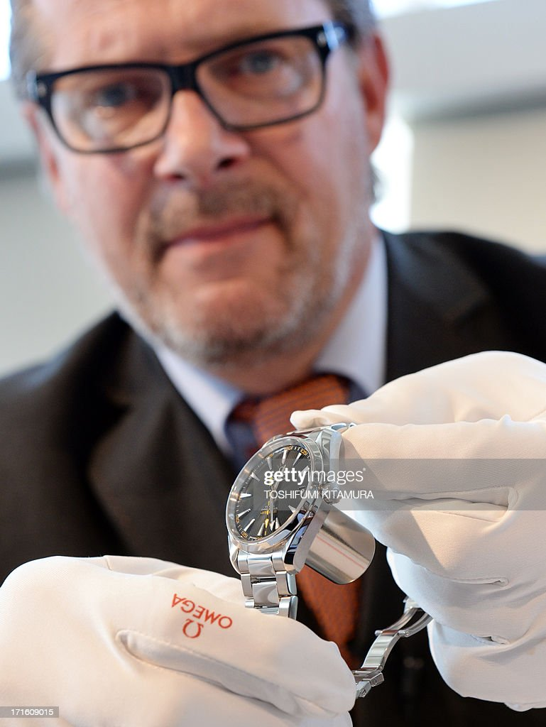 OMEGA vice president and head of product development Jean-Claude Monachon demonstrates the company's new anti-magnetic watch, 'Omega Seamaster Aqua Terra 15000 Gauss' working correctly with a strong neodymium magnet on its back during a press preview in Tokyo on June 27, 2013. Omega will introduce the anti-magnetic watches on the Japanese market from November this year.