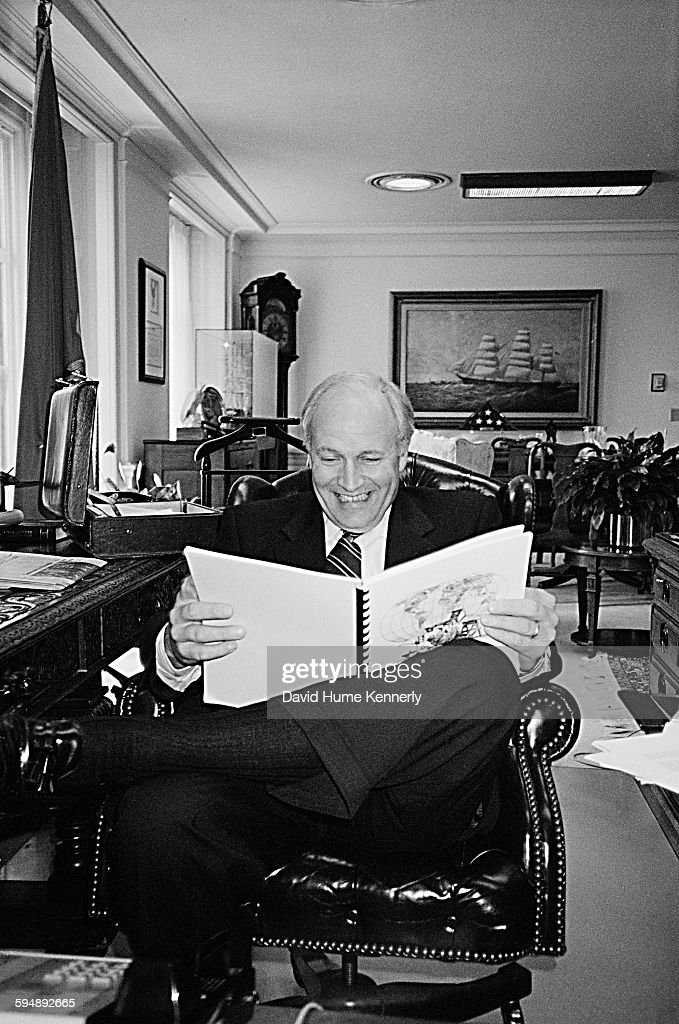 Vice President Dick Cheney laughs while reading a collection of Pluggers panel comics in his office circa 2001 in Washington, DC.