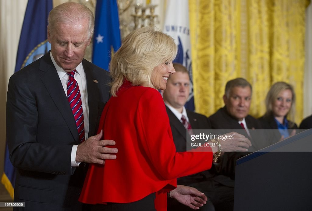 US Vice President Joe Biden (L) and his wife, Jill Biden (R), during an event highlighting Joining Forces hiring initiative for military veterans and spouses in civilian jobs in the East Room of the White House in Washington, DC, on April 30, 2013. Since President Obama challenged American businesses to hire US military veterans and spouses in August 2011, they have hired or trained 290,000 military veterans and spouses and now pledge to hire or train an additional 435,000 veterans and military spouses by 2018. AFP PHOTO / Saul LOEB