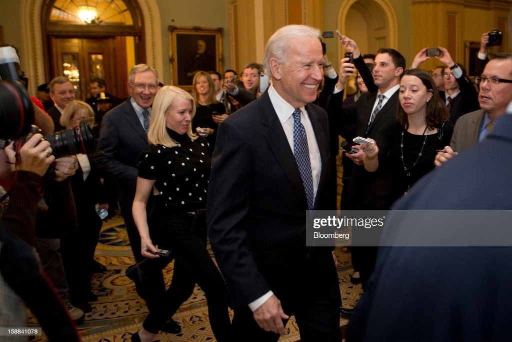 U.S. Vice President Joe Biden arrives to a Democratic caucus meeting with Senator Harry Reid, a Democrat from Nevada, left, at the U.S. Capitol in Washington, D.C., U.S., on Monday, Dec. 31, 2012. Biden arrived at the Capitol to present a budget deal to wavering Democrats, in advance of a possible vote by 10:30 p.m. tonight, with tax increases for almost every U.S. worker set to start tomorrow. Photographer: Andrew Harrer/Bloomberg via Getty Images