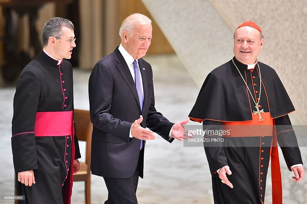 US Vice President Joe Biden (C) flanked by Cardinal Gianfranco Ravasi arrives to deliver a speech and to attend an audience of Pope Francis to the participants of the International Conference on the Progress of Regenerative Medicine and Its Cultural Impact, on April 29, 2016 at the Paul VI audience hall in Vatican. / AFP / VINCENZO