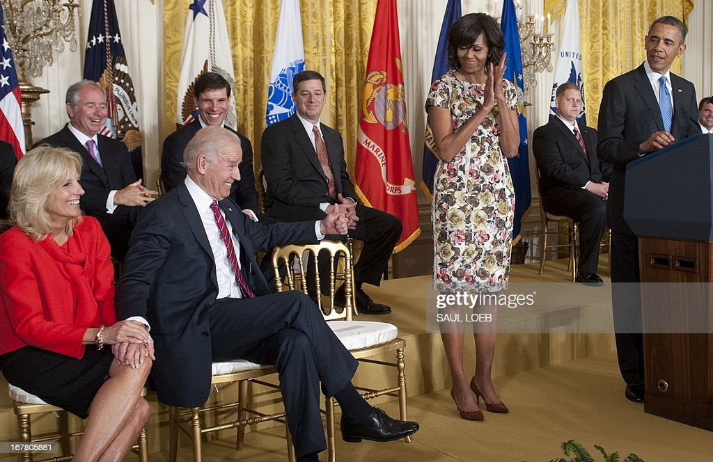US Vice President Joe Biden (2L) gives a thumbs-up alongside his wife, Jill Biden (L), as President Barack Obama speaks alongside First Lady Michelle Obama during an event highlighting Joining Forces hiring initiative for military veterans and spouses in civilian jobs in the East Room of the White House in Washington, DC, on April 30, 2013. Since President Obama challenged American businesses to hire US military veterans and spouses in August 2011, they have hired or trained 290,000 military veterans and spouses and now pledge to hire or train an additional 435,000 veterans and military spouses by 2018. AFP PHOTO / Saul LOEB