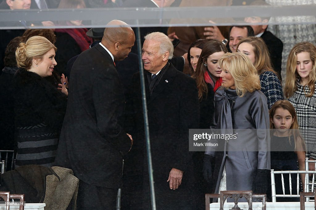 U.S. Vice President Joe Biden (C) greets Michelle Obama's brother Craig Robinson as Dr. Jill Biden (R) watches, as the presidential inaugural parade winds through the nation's capital January 21, 2013 in Washington, DC. Barack Obama was re-elected for a second term as President of the United States.