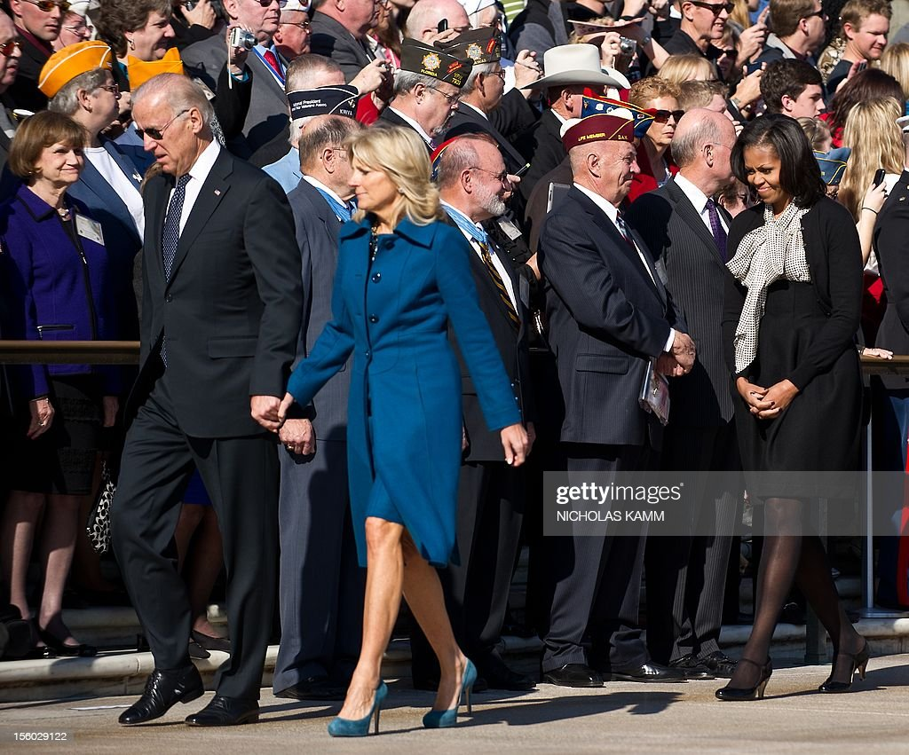 US Vice President Joe Biden (L), his wife Jill and First Lady Michelle Obama (R) arrive at a wreath-laying ceremony for Veterans' Day at Arlington National Cemetery in Arlington, Virginia, on November 11, 2012. AFP PHOTO/Nicholas KAMM