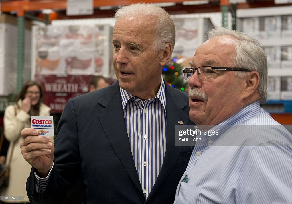 US Vice President Joe Biden holds up his Costco card alongside Costco co-founder Jim Sinegal (R) during a visit to a Costco store on a shopping trip in Washington, DC, on November 29, 2012. Biden made the visit to the first Costco store located in Washington, DC, during its grand opening. AFP PHOTO / Saul LOEB