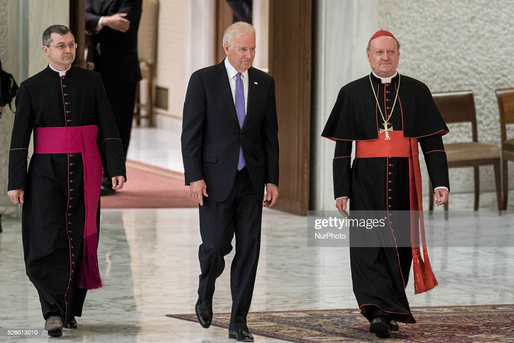 US Vice President Joe Biden (C) is flanked by Cardinal Gianfranco Ravasi (R) as he arrives to attend a special audience celebrates by Pope Francis with participants at a congress on the progress of regenerative medicine and its cultural impact in the Paul VI hall in Vatican City, Vatican on April 29, 2016.