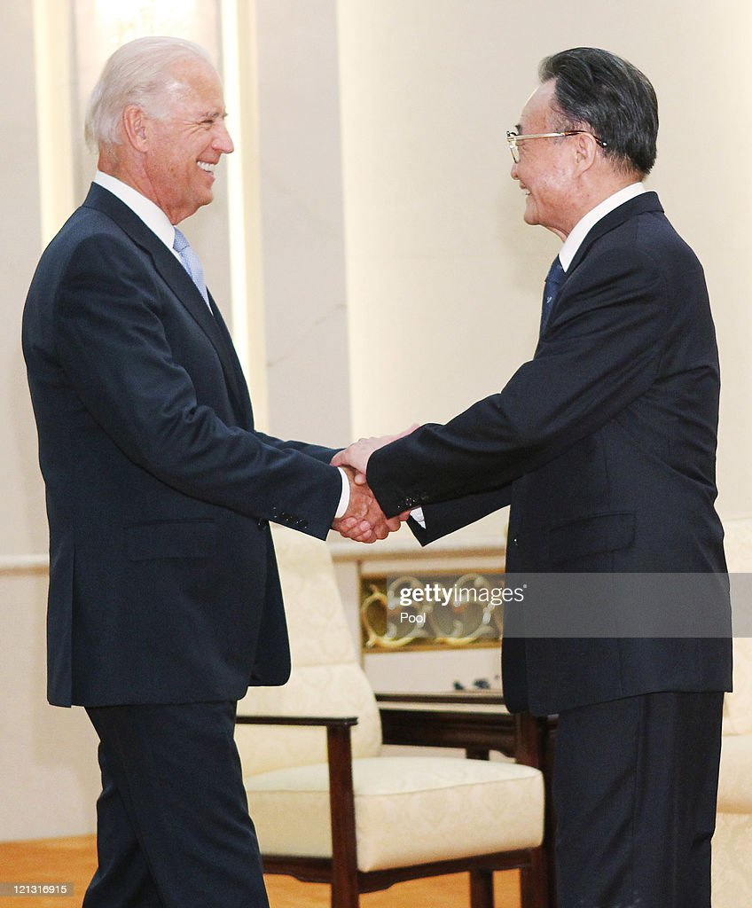 US Vice President Joe Biden (L) is greeted by Chinese National Peoples Congress Standing Committee Chairman <a gi-track='captionPersonalityLinkClicked' href=/galleries/search?phrase=Wu+Bangguo&family=editorial&specificpeople=604934 ng-click='$event.stopPropagation()'>Wu Bangguo</a> ahead of their meeting at the Great Hall of People on August 18, 2011 in Beijing, China. Biden will visit China, Mongolia and Japan from August 17-25.
