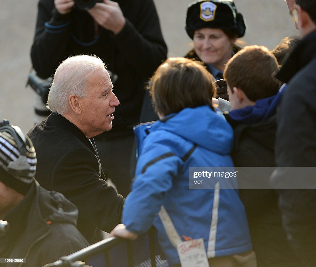 U.S. Vice President Joe Biden, left, stops to speak to a spectator during the Inauguration Parade for the second term of U.S. President Barack Obama in Washington, D.C., Monday, January 21, 2013.