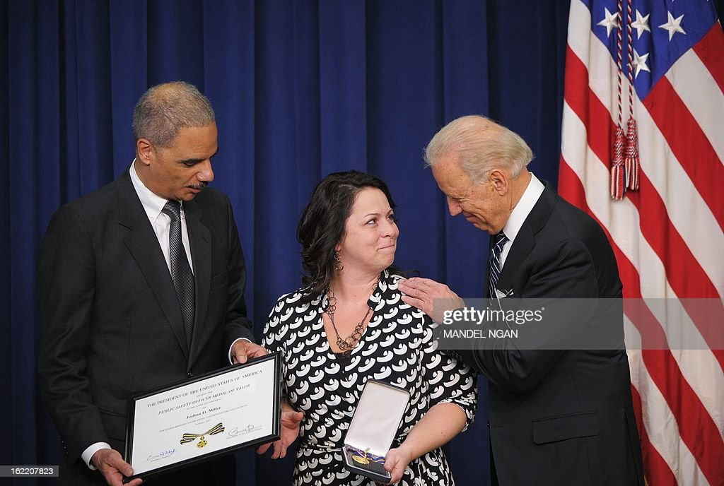 US Vice President Joe Biden (R) looks at Angela Miller, the wife of fallen Trooper Joshua Miller of the Pennsylvania State Police, while he and Attorney General Eric Holder (L) present her with the Public Safety Officer Medal of Valor for her husband during a ceremony on February 20, 2013 in the South Court Auditorium of the Eisenhower Executive Office Building, next to the White House, in Washington, DC. The medal is the highest national award for public safety officers who have shown exceptional courage, regardless of their own safety, to protect or save a human life. AFP PHOTO/Mandel NGAN