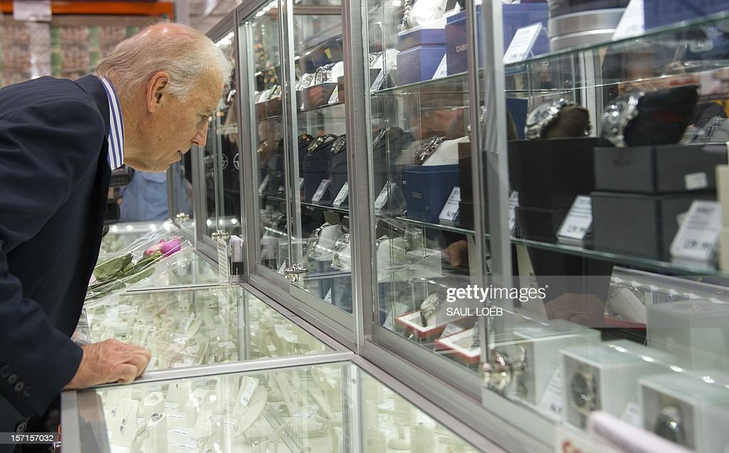 US Vice President Joe Biden looks at watches and jewelry during a visit to a Costco store on a shopping trip in Washington, DC, on November 29, 2012. Biden made the visit to the first Costco store located in Washington, DC, during its grand opening. AFP PHOTO / Saul LOEB